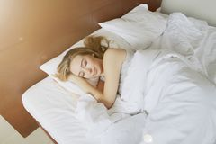 Foto de la luz del sol de la muchacha durmiente en la cama blanca Foto de archivo