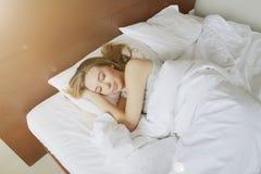Foto de la luz del sol de la muchacha durmiente en la cama blanca Foto de archivo libre de regalías
