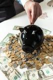 Foto de la mano que pone la moneda en la hucha negra Fotografía de archivo libre de regalías