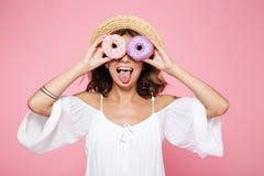 Foto de la muchacha bonita divertida en el sombrero de paja que mira con el spri dos Fotos de archivo libres de regalías
