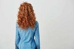 Foto de la muchacha con el pelo rizado rojo que se coloca de nuevo a cámara sobre el fondo blanco Copie el espacio Imagen de archivo libre de regalías