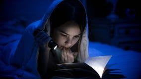 Foto de la muchacha con la linterna que lee el libro asustadizo debajo de la manta Foto de archivo libre de regalías