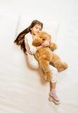 foto de la muchacha durmiente linda que abraza el oso de peluche Imágenes de archivo libres de regalías