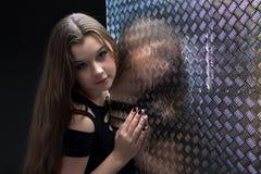 Foto de la muchacha en vestido negro cerca de la pared Fotografía de archivo libre de regalías
