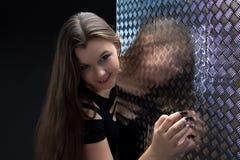 Foto de la muchacha sonriente en vestido negro cerca de la pared Fotos de archivo