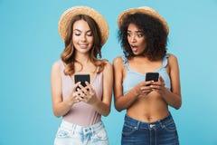 Foto de la mujer afroamericana curiosa que mira a escondidas en el teléfono móvil imagen de archivo
