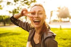 Foto de la mujer deportiva feliz 20s en bluetooth que lleva de la ropa de deportes imagen de archivo