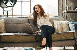 Foto de la mujer feliz que se sienta en el sofá delante del ordenador portátil abierto Foto de archivo libre de regalías