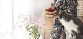 Foto de la mujer joven feliz que se coloca en la cocina cerca de la ventana en hogar y gato Foco en las crepes Copie el espacio Fotografía de archivo