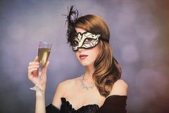 Foto de la mujer joven hermosa en máscara con la copa de champag Fotografía de archivo