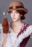 Foto de la mujer joven hermosa en vestido del vintage con magnificar Fotos de archivo libres de regalías
