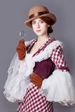 Foto de la mujer joven hermosa en vestido del vintage con magnificar Foto de archivo