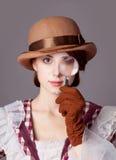 Foto de la mujer joven hermosa en vestido del vintage con magnificar Fotografía de archivo