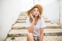 Foto de la mujer joven hermosa que se sienta en las escaleras de la calle el día de verano y que tiene conversación móvil en smar fotografía de archivo libre de regalías