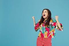 Foto de la mujer morena brillante emocionada en ropa casual colorida en el fondo azul fotografía de archivo libre de regalías