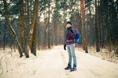 Foto de la mujer sonriente en sombrero con la mochila sobre bosque del invierno imagen de archivo