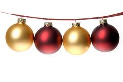 Foto de la Navidad del rojo y ornamentos del oro encadenados en cinta de la tela escocesa Fotos de archivo libres de regalías