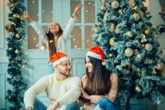 Foto de la Navidad de la familia sorprendida con los regalos Imagenes de archivo