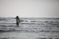 Foto de la persona que practica surf joven con el tablero de resaca Sirva la situación en el mar y las ondas de la mirada Aliste  Fotos de archivo