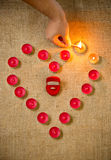 Foto de la persona que se enciende encima de velas en la forma del corazón Imágenes de archivo libres de regalías