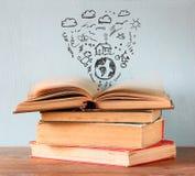 Foto de la pila de libros sobre la tabla de madera el libro superior está abierto con el sistema de iconos del infographics cree  Foto de archivo libre de regalías