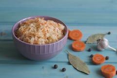 Foto de la placa de la chucrut y zanahorias y ajo en un azul brillante foto de archivo