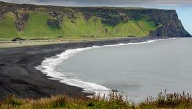 Foto de la playa volcánica oscura y del acantilado escarpado en el fondo fotografía de archivo
