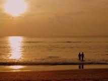 Foto de la puesta del sol de un muchacho y de una muchacha que caminan en el mar mientras que su reflexión se echa en la playa de Imagenes de archivo