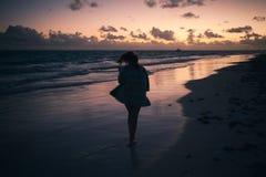 Foto de la silueta de la muchacha en la costa de Océano Atlántico Imagen de archivo