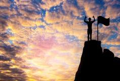 Foto de la silueta Una mano y una situación de la demostración del hombre en el acantilado imagenes de archivo