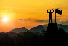Foto de la silueta Una mano y una situación de la demostración del hombre en el acantilado fotografía de archivo libre de regalías