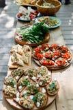 Foto de la tabla de madera con los bocados, bocadillos, crepes con las verduras Fotos de archivo libres de regalías