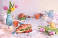 Foto de la vendimia Un desayuno de la familia de cruasanes con el arugula y queso y café aromático, huevos de diversos colores Ra Fotografía de archivo