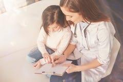 Foto de la visión superior del paciente atento mientras que se sienta cerca de enfermera imágenes de archivo libres de regalías