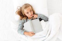 Foto de la visión superior de la niña pensativa que miente en cama con gris Fotografía de archivo
