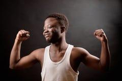 Foto de la vista lateral del hombre del Afro con los ojos cerrados y de la sonrisa mostrando su bíceps Fotos de archivo libres de regalías