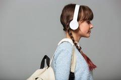 Foto de la vista lateral de la música que escucha de la muchacha con los auriculares Imagenes de archivo
