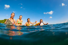 Foto de las muchachas felices de la persona que practica surf que se sientan en los tableros de resaca Fotos de archivo libres de regalías