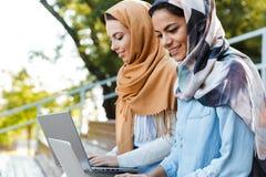 Foto de las muchachas islámicas felices que llevan los headscarfs que estudian en parque foto de archivo