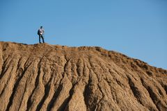 Foto de longe do homem do turista com as varas para andar no monte contra o céu azul Fotografia de Stock