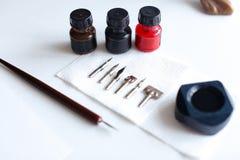 Foto de los accesorios para la caligrafía y las letras en el tabl blanco Fotografía de archivo libre de regalías