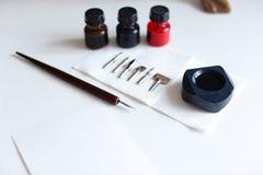 Foto de los accesorios para la caligrafía y las letras en el tabl blanco Foto de archivo libre de regalías
