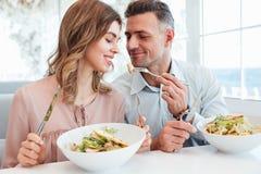 Foto de los pares románticos adultos que cenan y que comen los salats w Fotos de archivo