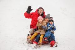 Foto de padres felices con la hija y el hijo que se sientan en la tubería en invierno Imágenes de archivo libres de regalías