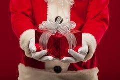 Foto de Santa Claus buena que da el presente de Navidad y que mira la leva Foto de archivo