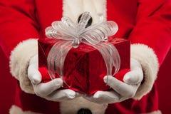 Foto de Santa Claus buena que da el presente de Navidad y que mira la leva Fotografía de archivo libre de regalías