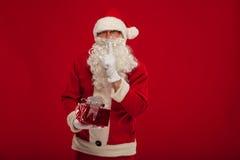Foto de Santa Claus buena que da el presente de Navidad y que mira la leva Foto de archivo libre de regalías