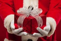 Foto de Santa Claus buena que da el presente de Navidad y que mira la leva Imagen de archivo