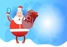 Foto de Santa Claus With Reindeer Making Selfie, cartão do feriado do Natal do ano novo Fotos de Stock
