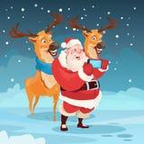 Foto de Santa Claus With Reindeer Making Selfie, cartão do feriado do Natal do ano novo Imagem de Stock